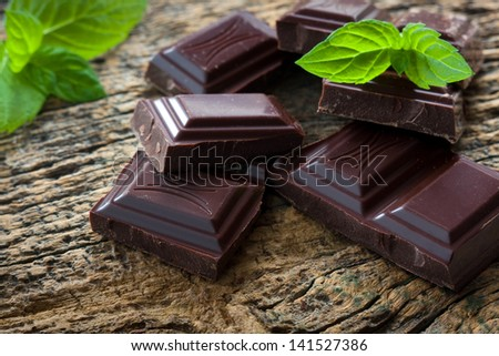 Dark chocolate pieces with a leaf of mint on wooden background