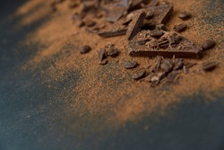 Dark chocolate stack, chips and cocoa powder with coffee beans on a dark background. Confectionery and food concept. Top view, copy space, selective focus.