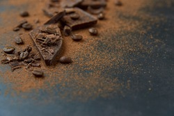 Dark chocolate stack, chips and cocoa powder with coffee beans on a dark background. Confectionery and food concept. Top view, copy space, selective focus..