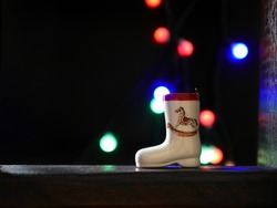 Dark christmas background with a Christmas tree toy ceramic boot on a wooden board. Glare garlands of lights on a blurry side. Selective focus on the toy.