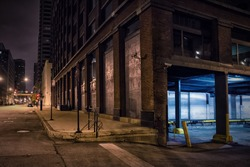 Dark city downtown street corner with an industrial warehouse loading dock at night.