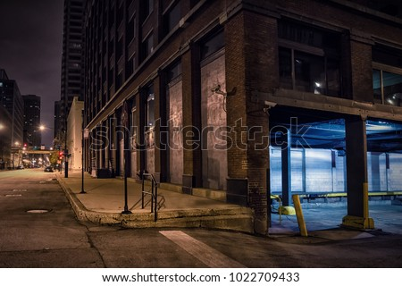 Dark city downtown street corner with an industrial warehouse loading dock at night. #1022709433