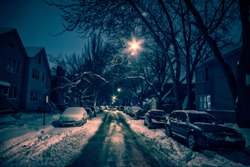 Dark city street with trees, snow and parked cars at night in the winter.