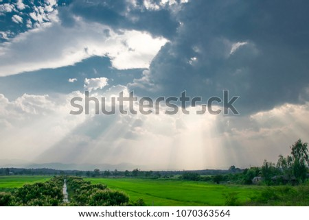 dark clouds and beautifull sun lights over Field  #1070363564