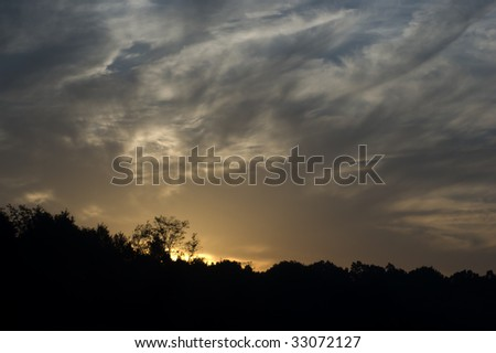 dark clouds at sunrise over trees