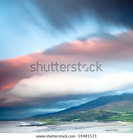 dark clouds during sunset over Irish coast Dingle peninsula Kerry district hills and beach long exposure image give a dramatic look