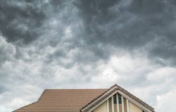 Dark clouds going to heavy rain over the house roof.