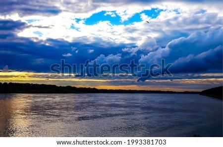 Dark clouds over the river. River in cloudy day. River dark clouds landscape
