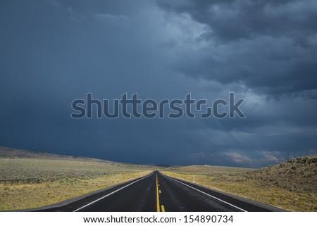 Dark clouds threatening a rain storm above desert highway