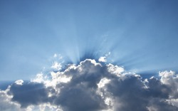 Dark clouds with sun rays over a blue sky