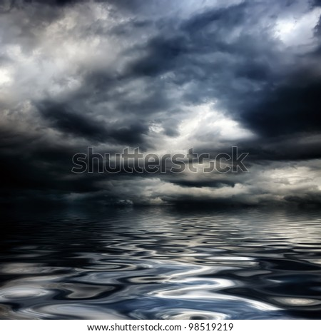 dark cloudy stormy sky with clouds and waves in the sea - global warming concept