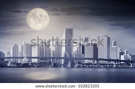 Dark color processed panorama of a full moon rising in the night sky over the city of Miami, with downtown buildings and Biscayne bay bridge.