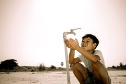 Dark color tone. Close up Asian boy open metal blue water faucet on hot and dry empty land. Water shortage concept.