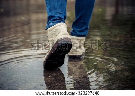 Dark color tone. Traveller female shoe walk on water on concrete floor after heavy raining.