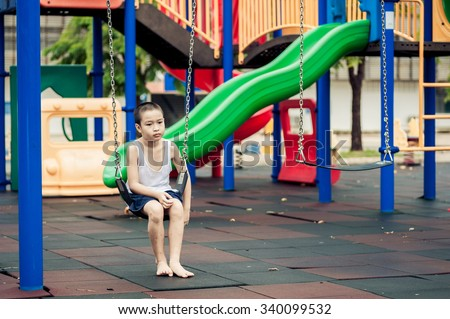 Dark color tone, unhappy young Asian boy sit and waiting on swinging at outdoor playground.