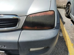 Dark colored plastic car headlight torn and damaged. Headlamp tint able to prevent the headlamp from turning into yellowish, protect the headlamp from stone chips and refine the appearance of the car.