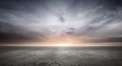 Dark Concrete Floor Background with Dramatic Sky Clouds and Sunset Horizon