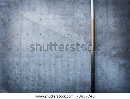 Dark concrete wall with metal pipe.