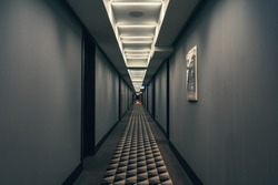 Dark corridor with illumination on ceiling. Tunnel view of empty hotel corridor in night time, toned