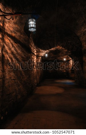Dark corridors of old time castle dungeon light with few lamps #1052547071