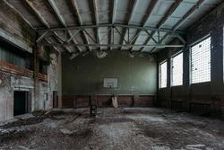 Dark creepy ruined gymnasium in abandoned school.
