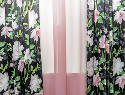 Dark curtains with a floral pattern and pink tulle on the living room window.