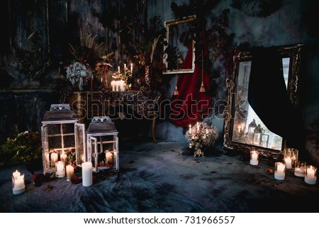 dark decor with dried flowers, vases, chandeliers, textured fabrics against the wall with a golden frame, a wooden table in a luxurious royal Victorian style, burning candles in old lanterns