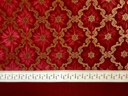Dark deep red and bright burgundy wallpaper with golden ornament and white fretwork edging, straight view closeup. Red and golden luxury diamond shape rich backdrop. Vintage wallpaper texture