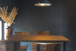 Dark dining table with wooden chair and dry flower in vintage design room