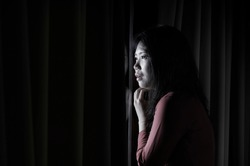 dark dramatic portrait of young beautiful scared and depressed Asian Chinese woman feeling overwhelmed and in panic lockdown alone at home during covid-19 virus outbreak quarantine