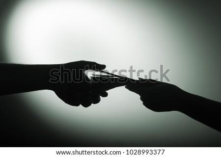 dark economy. Two hands with money Foto stock ©