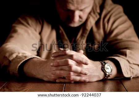 Dark, emotional image of clasped hands on troubled man