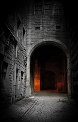 Dark empty courtyard in Edinburgh, Scotland with mysterious glowing archway