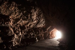 Dark empty road goes through the cave with glowing end