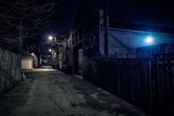 Dark empty scary urban city street alley with vintage buildings at night