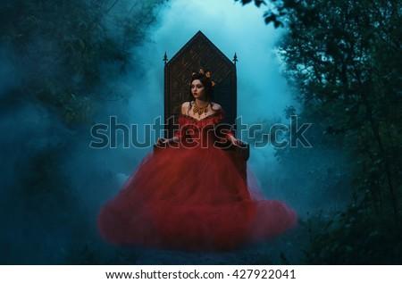 Stock Photo dark evil queen sitting on a luxurious throne,dark boho,  wild Princess in red dress , vampire , hip toning , creative color,dark boho