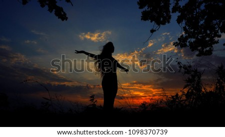 Dark female silhouette doing yoga asanas in evening sky background. Concept of meditating before sleeping and relaxing atmosphere.