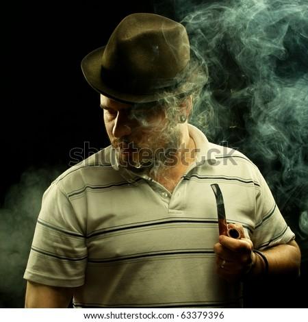 Dark fine art portrait of a smoking man in hat. With tobacco pipe.