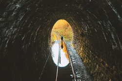 Dark flooded single track tunnel with a standing man. Urbexer in old abandoned railway tunnel.