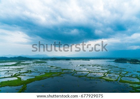 Dark fluffy blue rain clouds forming over floating islands of plants in Loktak Lake, Manipur, India during monsoon season