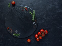 Dark food background with empty stone round plate,fresh rosemary,fresh cherry tomatoes,dry chilli peppers and sea salt on black background.Top view with copy space.