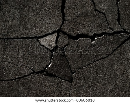 Dark fractured concrete surface closeup background. - stock photo