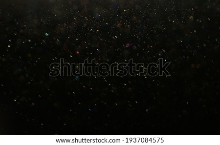 Dark glitter colorful  lights background. light in black background. Dust  in the space. hole in the wall. Foto d'archivio ©