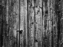 Dark gloomy black and white background of old locked up barn door with a latchkey