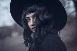 Dark gothic witch in black attire walking in the woods