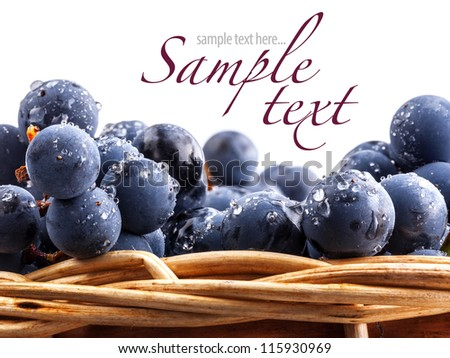 Dark grapes with leaves in a wicker basket, on white background