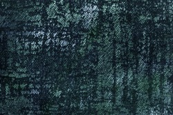 Dark green and blue fluffy background of soft, fleecy fabric. Texture of emerald textile backdrop with shiny pattern, closeup.