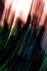 Dark green and blue light streaks on black leading up into fiery sky - abstract motion blurred background / texture