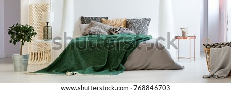 Dark green blanket on bed with patterned pillows in boho style bedroom with lamp on table and plant in bucket #768846703