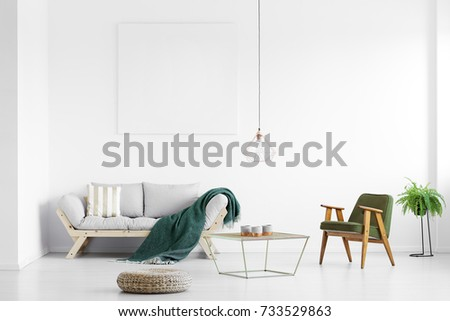 Dark green blanket thrown on grey sofa in bright living room with empty poster and armchair